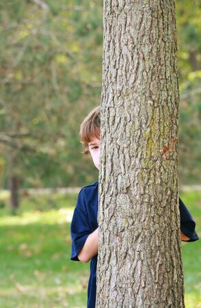 hide and seek: Boy Peeking Around a Tree
