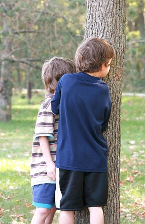 Boys Peeking Around Tree photo