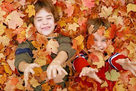 Jongens spelen in de bladeren