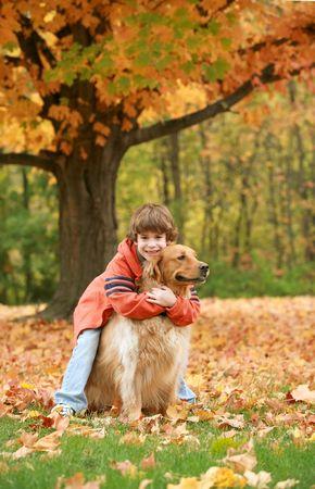 autumn dog: Boy Hugging Golden Retriever