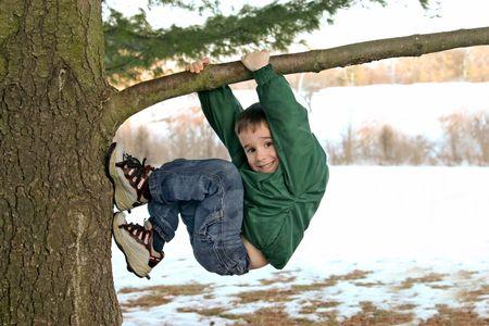 enfants qui rient: Boy escalade un arbre en hiver