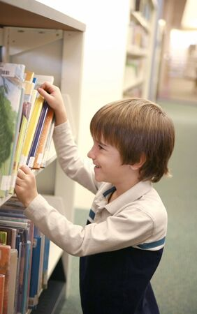 kid sitting: Boy Picking Out a Library book Stock Photo