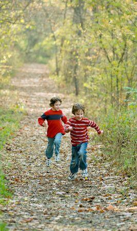 hermanos jugando: Boys Racing in the Woods  Foto de archivo