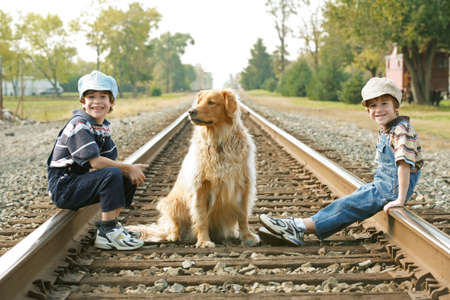 Boys And Dog Sitting on Train Tracks Banque d'images