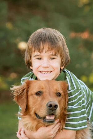 Boy Hugging Golden Retriever photo