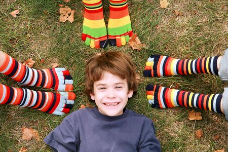 stockings feet: Boy Smiling Surrounded by Toe Socks Stock Photo