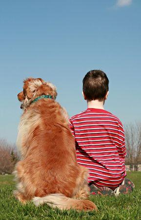 Boy and Dog Sitting on a Hill
