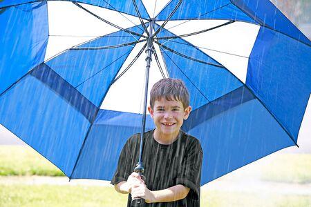 Boy in the Rain Under an Umbrella photo