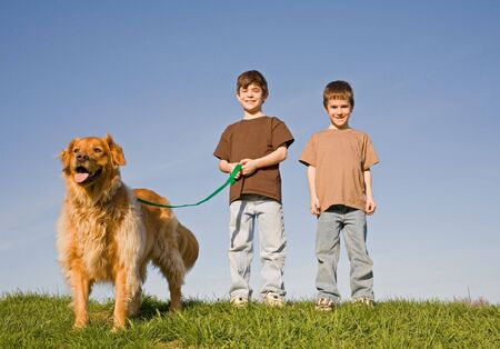 friends and family: Boys Walking the dog Stock Photo