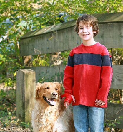 dogs playing: Young Boy with a Golden Retriever Stock Photo