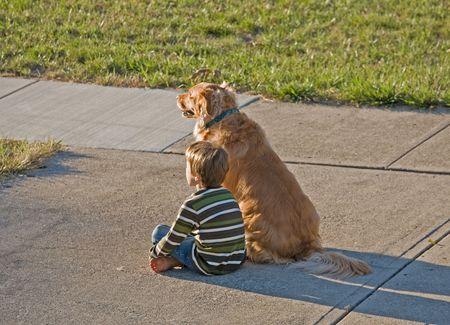 perros jugando: Little Boy viendo el sol ir hacia abajo con el mejor amigo  Foto de archivo