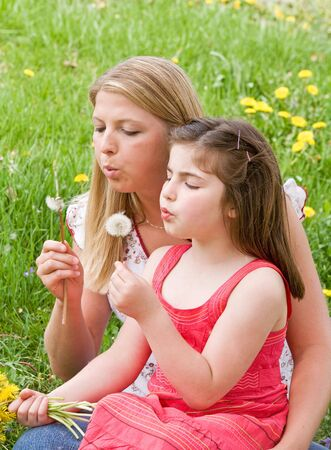 Mother and Daughter Blowing Dandelion Seeds Together Stock Photo - 2993536