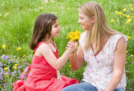 giving season: Daughter Giving Mother Flowers Stock Photo