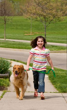 walking down: Girl Walking Down the Sidewalk With Dog Stock Photo
