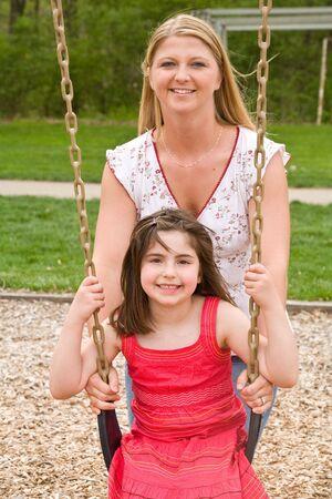 Mom Pushing Daughter on Swing photo