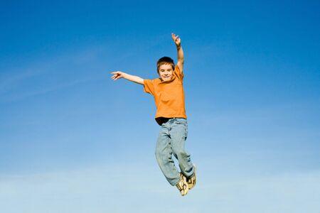 ni�o saltando: Boy saltos en el cielo  Foto de archivo
