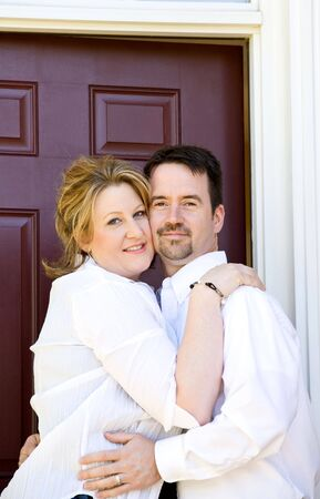 front house: Happy Couple Standing By Front Door