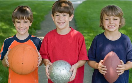 child model: Three Boys Holding Sports Balls Stock Photo