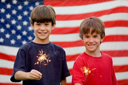 fourth july: Boys at Twilight Holding Sparklers in Front of Flag Stock Photo