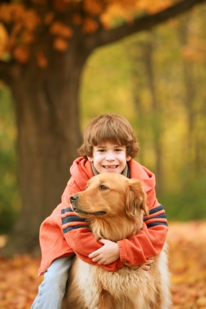 Boy Hugging Dog in the Fall Stock Photo - 3336890