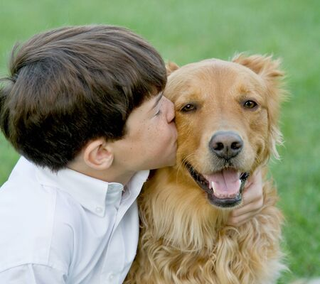Little Boy Kissing Dog Banque d'images
