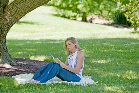 Young Woman Reading Under a Tree Stock Photo - 3351491