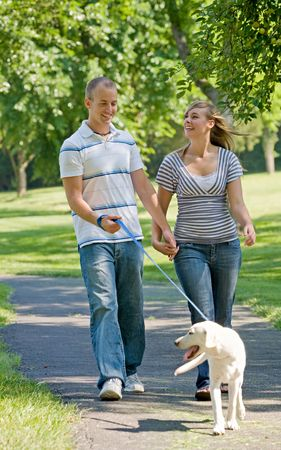 family and friends: Young Couple Walking Dog Stock Photo