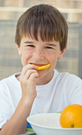 Boy manger tranche d'orange  Banque d'images - 3499925