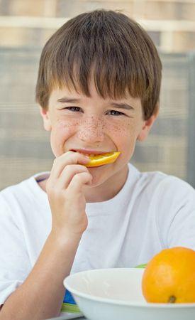 naranjas: Chico comer rebanada de naranja