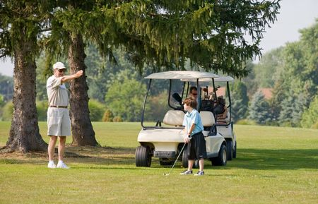 instructing: Grandpa Instructing Grandson in Golfing Stock Photo