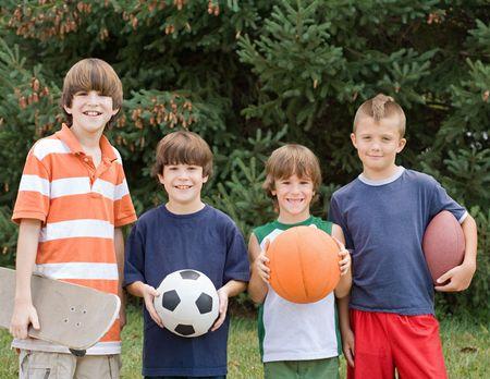 hermanos jugando: Cuatro diferentes deportes Foto de archivo