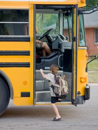 行き: 小さな男の子のバスに乗る 写真素材