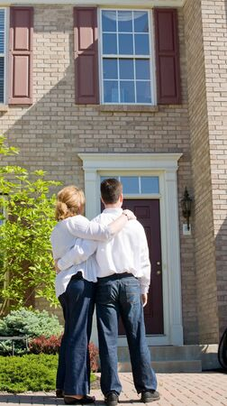 front of: Couple Looking at New Home Stock Photo