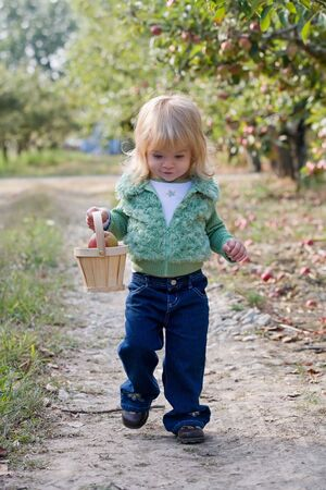 Little Girl Walking in Apple Orchard Stock fotó