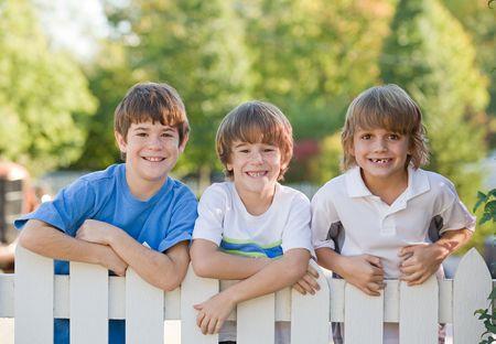 Trois jeunes garçons sur un piquet de clôture blanche Banque d'images - 3775992