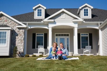 fachada de casa: Familia feliz frente a su casa