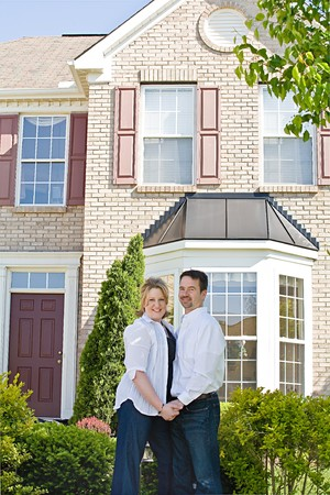 front of: Happy Couple Standing in Front of Home Stock Photo