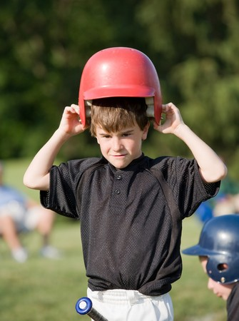 Little Boy Putting on Helmet Getting Ready to Hit Stock Photo - 4127002