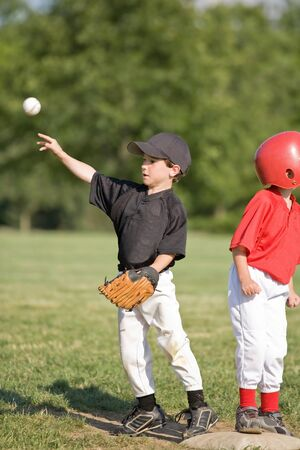 Little Boy Throwing Baseball From First Base