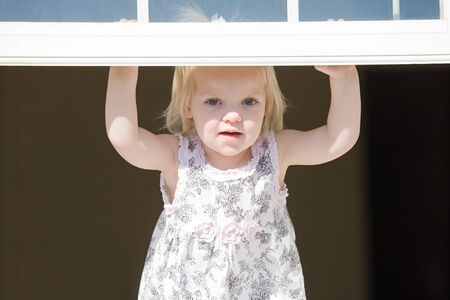 opening window: Ni�a Mirando por la ventana Foto de archivo