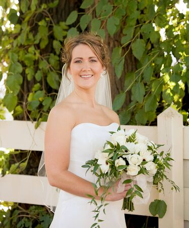 Stunning Bride Holding a Bouquet in Front of a White Fence photo