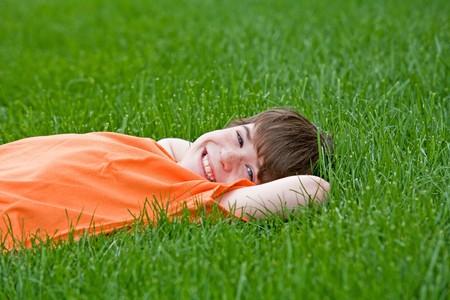草で横たわる少年 写真素材