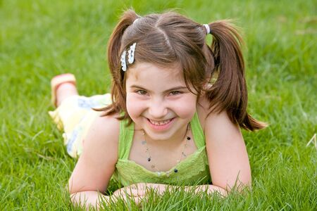 Little Girl Laying in the Grass Laughing Stock Photo - 4610936