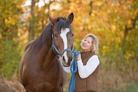autumn horse: Woman Looking at Horse Stock Photo