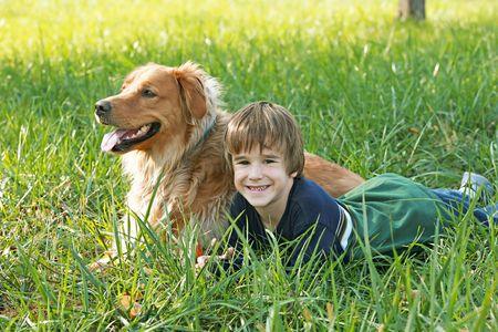 소년과 잔디에 누워있는 개