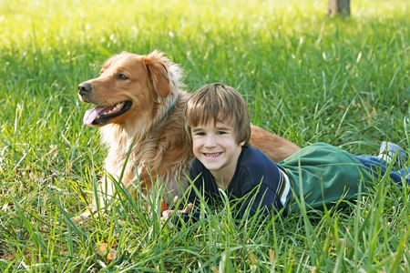 Boy Laying in the grass with Dog