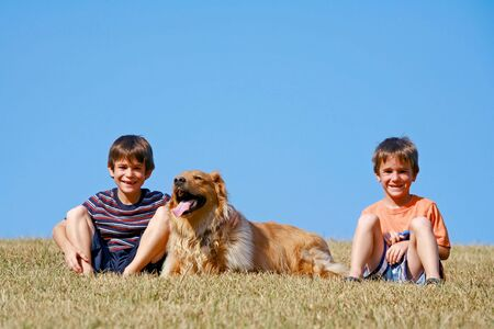 Boys and Dog Sitting on the Side of a Hill Stock Photo - 4661817