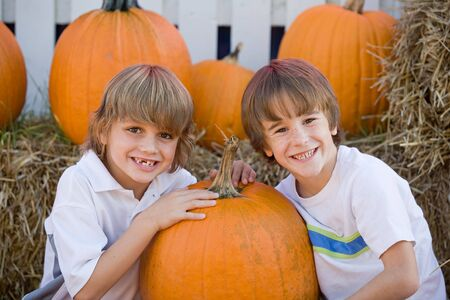 pumpkin face: Two Boys Smiling in a Pumpkin Patch Stock Photo