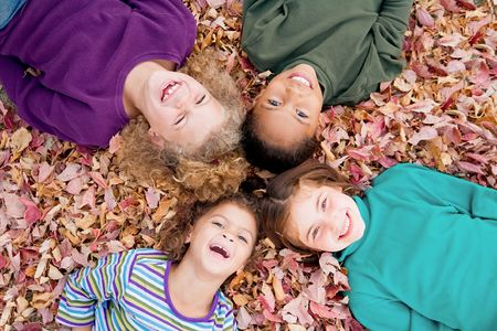 children at play: Four Girls Playing in Fall Leaves Stock Photo