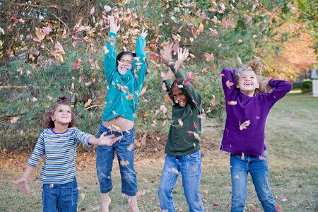 ni�as jugando: Muchachas, que jugar�n en las hojas se caen